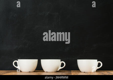 ceramic white coffee cups grouped on wooden floor texture with blackboard wall background showing retro style with - Stock Photo