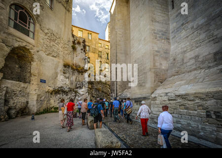A group of tourists walk along a narrow stone path between a stone and a rock wall in Avignon France in the Provence - Stock Photo