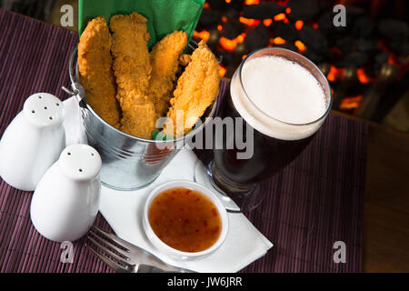 A pub/restaurant lunch/ snack of Hot and Spicy breaded Chicken fillets with a Sweet Chili dip and a glass of ale. - Stock Photo
