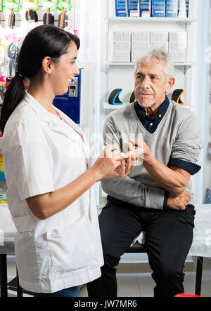 Senior male patient looking at female doctor checking his sugar level in clinic - Stock Photo