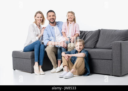 Happy young family with two children sitting together on couch isolated on white - Stock Photo