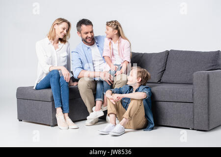 Happy young family with two children sitting together on sofa and smiling - Stock Photo