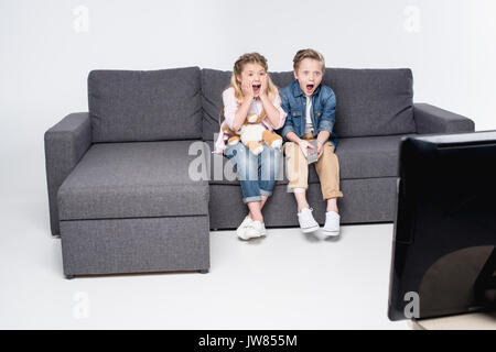 scared boy and girl sitting on sofa and watching tv together - Stock Photo