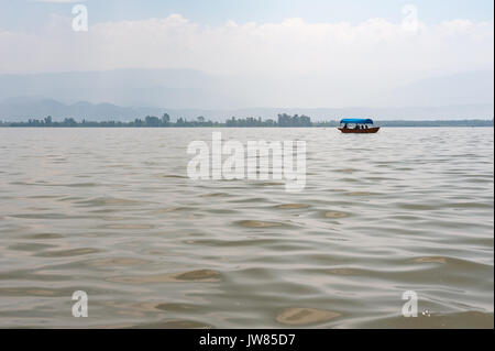 Small boat on a lake in the haze with mountains in the backgroun - Stock Photo