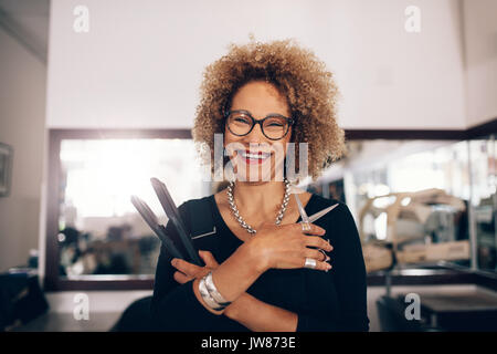 Hairdresser holding a hair straightener and scissors. Closeup of curly haired woman hairdresser in happy mood at - Stock Photo
