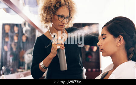 Woman hairdresser spraying hair setting liquid on her customer's hair. Young woman getting a stylish hairdo done - Stock Photo