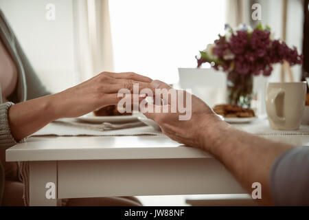 cropped view of senior couple holding hands during breakfast - Stock Photo