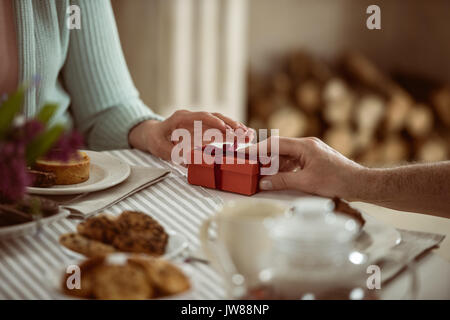 cropped view of senior husband presenting gift box to his wife - Stock Photo