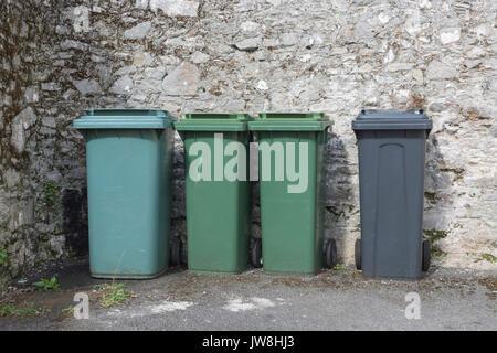 Row of four domestic wheelie-bins / wheely bins / rubbish bins beside a stone wall. Redundant data metaphor. - Stock Photo