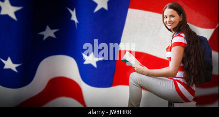 Student reading book in library against american flag with stripes and stars - Stock Photo