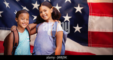 Portrait of smiling friends against close-up of red and white american flag - Stock Photo