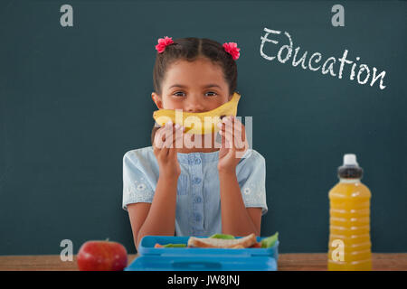 Girl holding banana at table against education text against white background - Stock Photo
