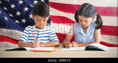 Children writing on books at table against close-up of an flag - Stock Photo