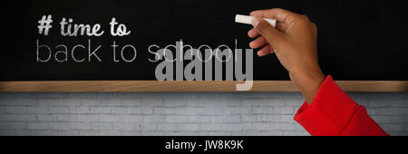 Cropped image of girl with hand raised holding chalk against blackboard on wall - Stock Photo