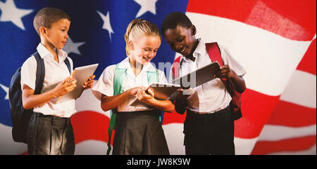 Students in uniforms using digital tablets against american flag with stripes and stars - Stock Photo