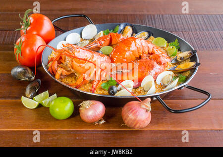 Gourmet seafood Valencia paella with fresh langoustine, clams, mussels and squid on savory saffron rice with peas - Stock Photo
