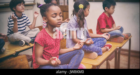 Pupils meditating in lotus position on desk in classroom at the elementary school - Stock Photo