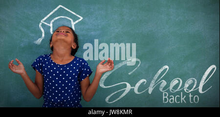 Back to school text over white background against happy girl with head back by blackboard - Stock Photo