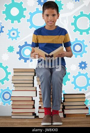 Digital composite of Boy reading and sitting on book tower in front of cog gear settings - Stock Photo