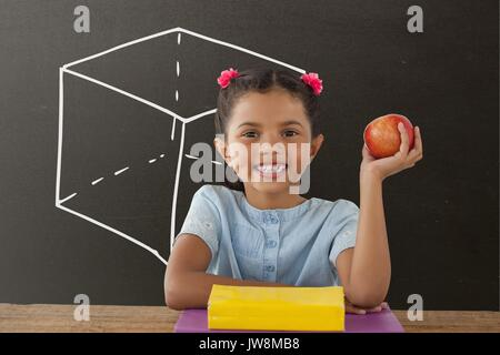 Digital composite of Happy student girl at table holding an apple against grey blackboard with school and education - Stock Photo