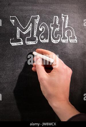 Digital composite of hand writing Math on blackboard - Stock Photo