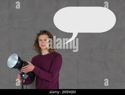 Digital composite of Photographer man with speech bubble against grey background - Stock Photo