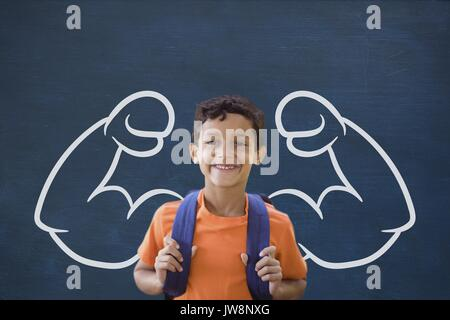 Digital composite of Happy student boy with fists graphic standing against blue blackboard - Stock Photo