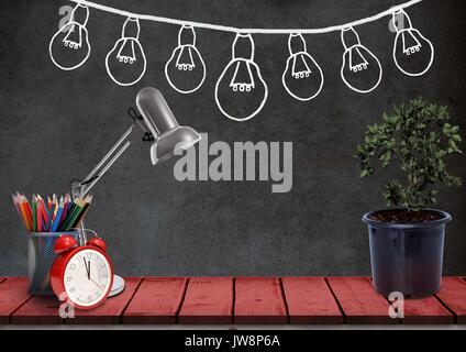 Digital composite of Desk foreground with blackboard graphics of light bulbs - Stock Photo