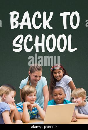 Digital composite of Students at table looking at a computer against green blackboard with back to school text - Stock Photo