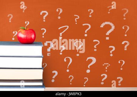 Digital composite of Books on the table against orange blackboard with question marks - Stock Photo