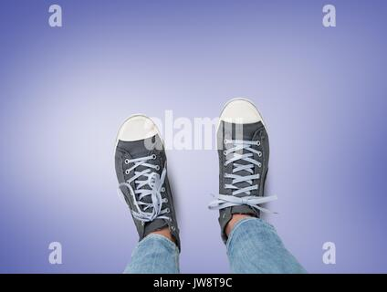 Digital composite of Grey shoes on feet with purple background - Stock Photo