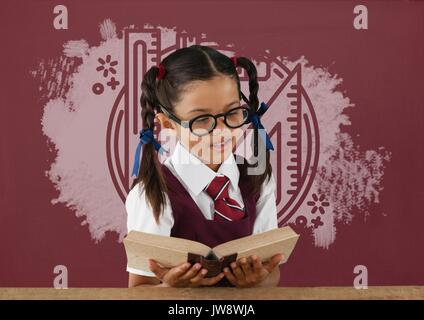 Digital composite of Student girl at table reading against red blackboard with education and school graphic - Stock Photo