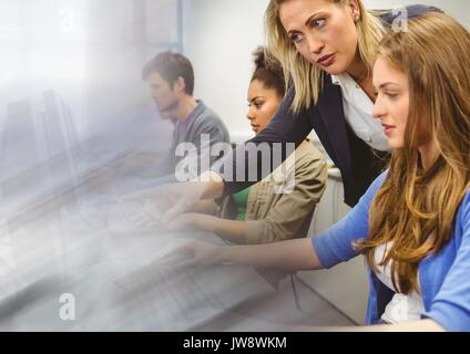 Digital composite of teacher with class on computers - Stock Photo