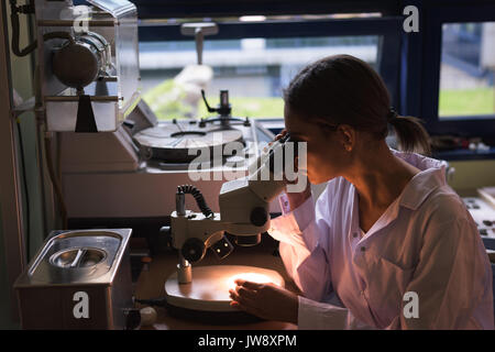 Female college student using microscope while practicing experiment in lab - Stock Photo