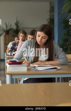 College students writing on book while sitting at desks during exam in classroom - Stock Photo