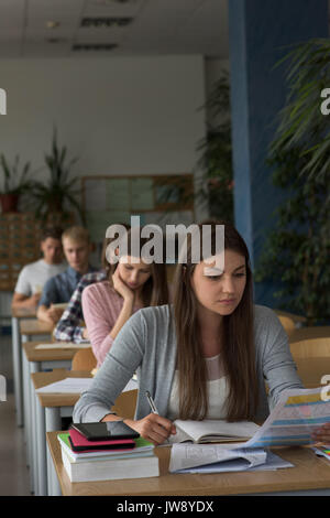 College students sitting at table during exam in classroom - Stock Photo