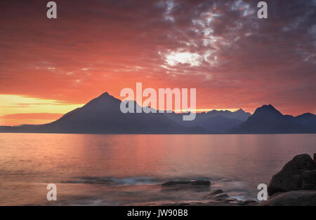 The Cuillin mountains from Elgol, Isle of Skye, with the sea and a spectacular sunset and fine cloud formations. - Stock Photo
