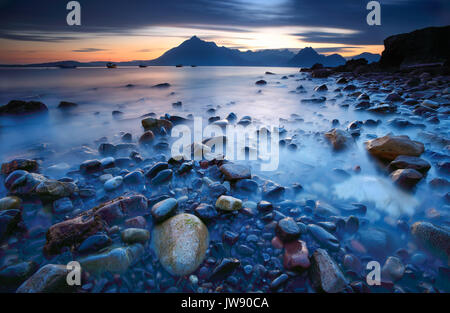 The Cuillin mountains from Elgol, Isle of Skye, with the colourful rounded stones in the foreground. - Stock Photo