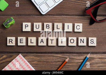 Office stuff and Society public relations idea spelled with blocks - Stock Photo