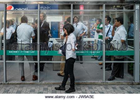 Asia, Japan, Tokyo, People smoking in a smoking area. - Stock Photo