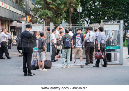 Asia, Japan, Tokyo, People smoking in a smoking area. - Stock Photo