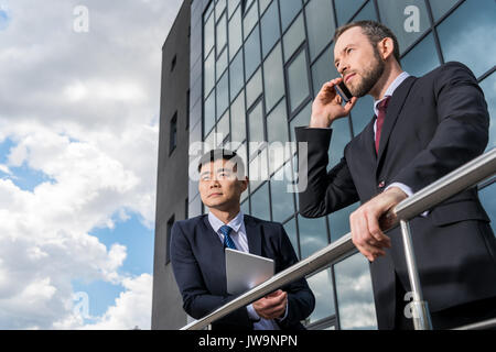 multicultural business team meeting and using smartphone and digital tablet outdoors near office building - Stock Photo