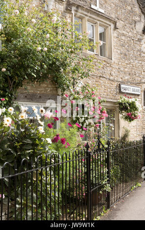 Colourful flowers cover a wall of a Cotswold stone built house in Minchinhampton Gloucestershire UK - Stock Photo