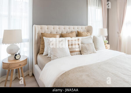 Bedroom in soft light colors. big comfortable double bed in elegant classic bedroom at home. - Stock Photo
