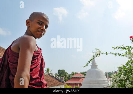 Dickwella, Sri Lanka, 04-15-2017: Young Buddhist monk on the background of a Buddhist pagoda looks at the camera - Stock Photo