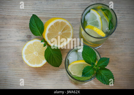 Refreshing drink with water, lemon, mint, ice in glasses on a wooden background. Homemade detox water - Stock Photo