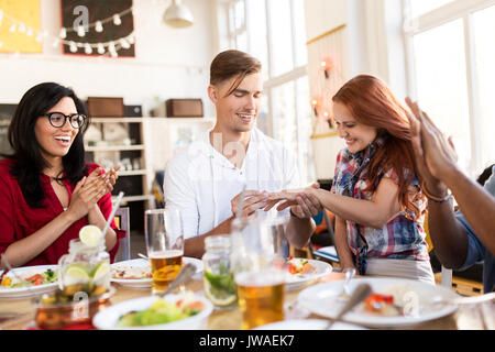 happy man doing proposal to woman at restaurant - Stock Photo