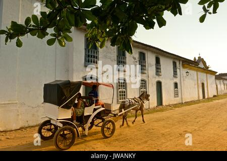 Tourists ride in a horse drawn carriage through the Historic Centre district of Paraty. - Stock Photo