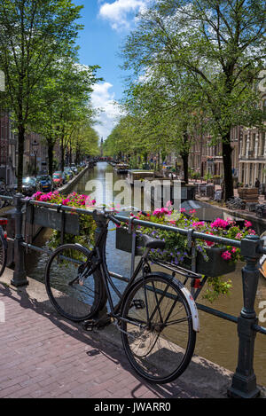 Old Dutch bicycle on a canal bridge, Amsterdam, North Holland, Netherlands - Stock Photo