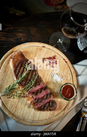 Sliced medium rare grilled steak on rustic cutting board with rosemary and spices , dark rustic metal background, - Stock Photo